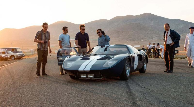 Ford racing team members gathered around a GT40 in Ford v Ferrari.