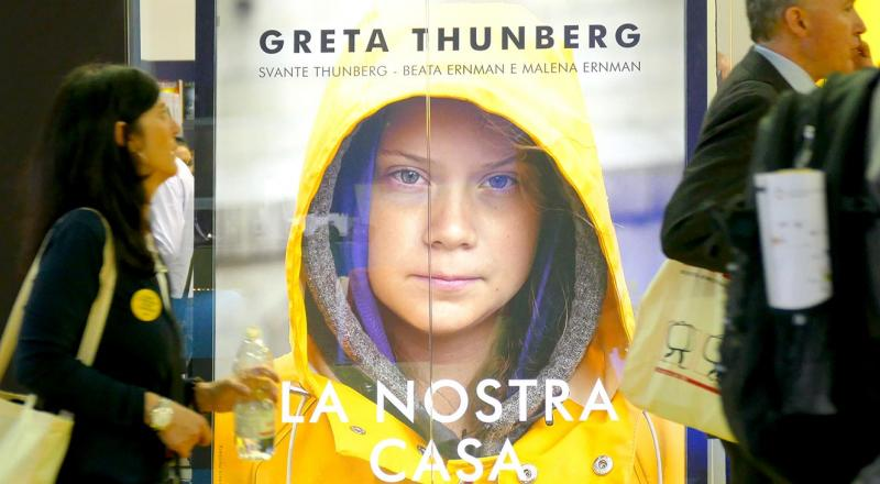Commuters pass by a poster of climate activist Greta Thunberg.